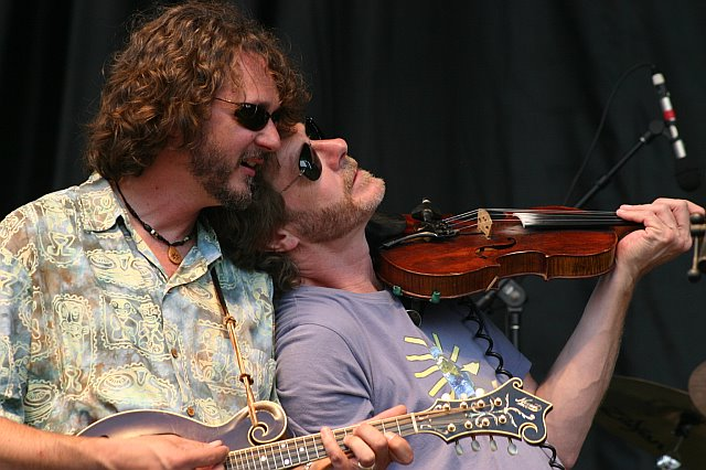 Sam Bush Rests His Head on Drew Emmitt's Shoulder